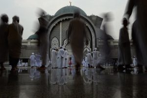 """This picture taken on March 20, 2016 shows Malaysian religious students walking at a corridor of the Federal Territory Mosque before offering prayers during a gathering for students who had successfully memorised the Muslim holy book the Koran in its entirety, in Kuala Lumpur.  Some 20,000 religious students from across the country attended the Koran recitation in honour of them attaining """"Hafiz"""", which means guardian memoriser of the Muslim holy book.    / AFP / MOHD RASFAN"""