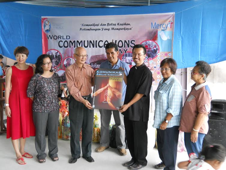 Fr Thomas (3rd from right) and Leong holding a poster specially designed for WCD 2016, with other SOCCOM members who attended the celebrations at St Philip Neri, Pekan Nabalu on May 8 (from left): Claudina Wong, Jenney Juanis, Ruben Sario (centre), Patricia Regis and Irene Obon.