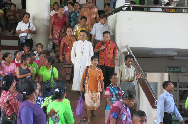 With their pastor in their midst, the migrant communities enter the parish centre for the fellowship, 16 Oct 2016.