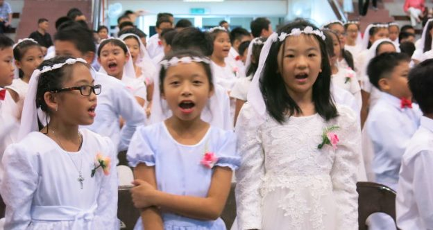 First communicants sing the song they learnt at the camp during the reception at the cathedral parish hall Oct 29.
