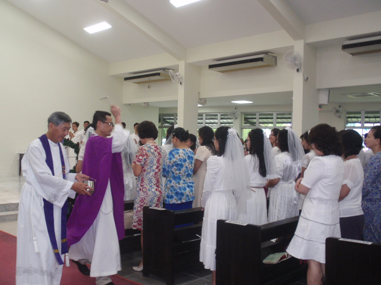 Abp Wong sprinkles the people with holy water during the rite of blessing.