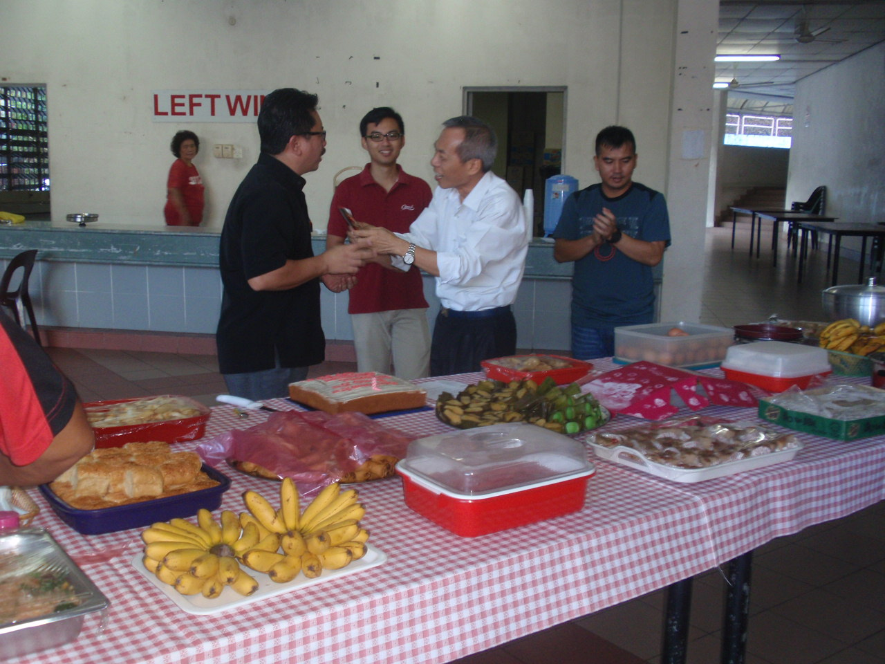 Christopher Voo (R) gives a token of appreciation to Fr Atin (L).