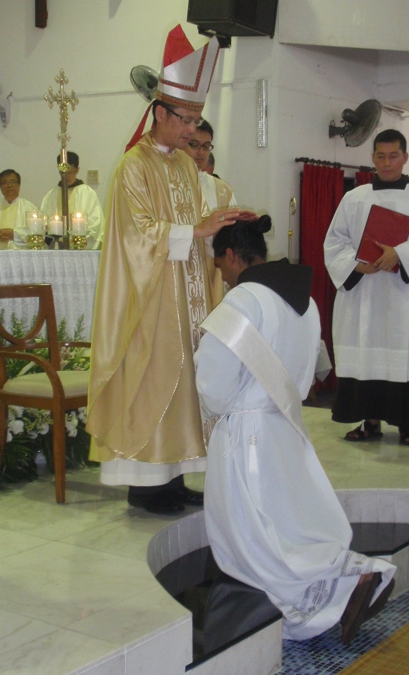 Abp Wong places his hands on the head of the ordinand during the rite of ordination.