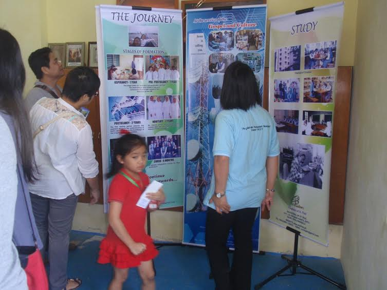 A child passes in front of the exhibit put up by the religious institutes.