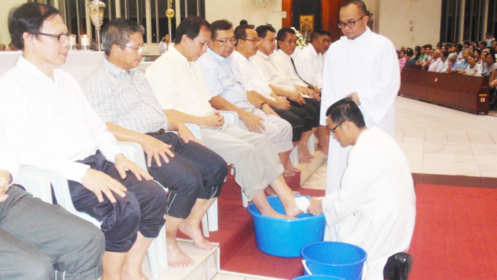Abp Wong dries the feet of one of the men after pouring water over them.