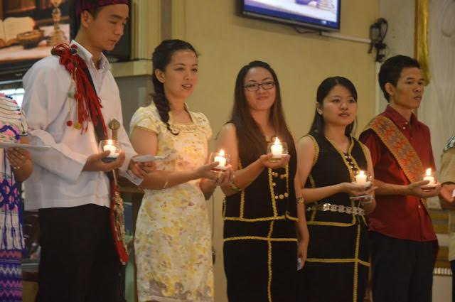 The graduates hold their lighted candles during the ceremony.
