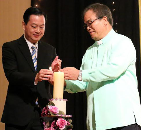 Funk (L) and Msgr Primus (R) light the candle at the commencement of the ceremony.