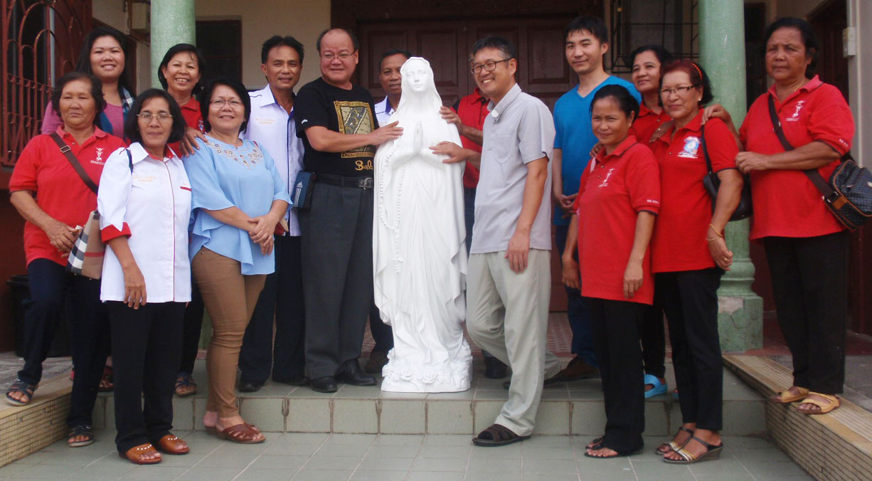 Fr Choi (right of statue) poses with Fr Anthony Mikat (left of statue) and others at the presentation ceremony.