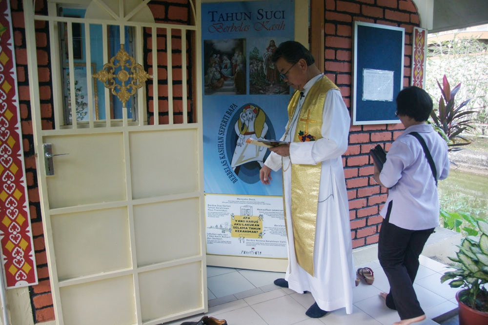 The bishop leads the rite of opening the door of mercy.