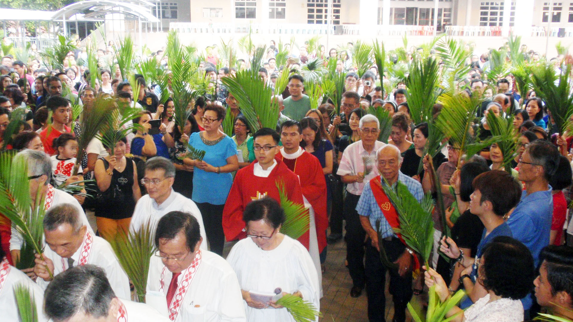 The people make the procession to the cathedral after the blessing of palms at the Sacred Heart Parish Centre foyer Mar 19.