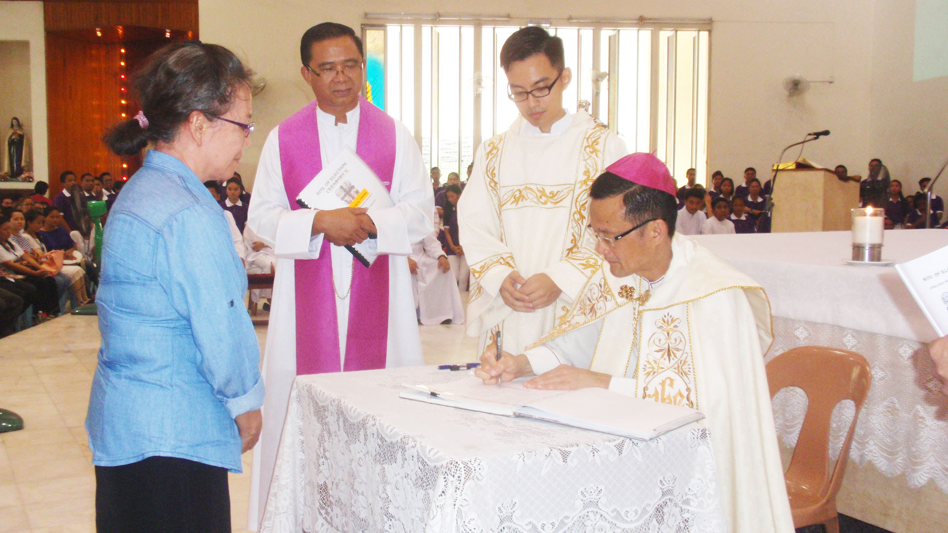 The prelate signs the Book of the Elect of one of the parishes.