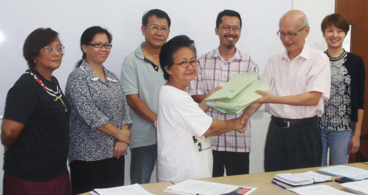 Outgoing head Irene Obon (front left) hands over the files to new head Datuk Joseph Leong (fron right) witnessed by the other members during the handing over ceremony.