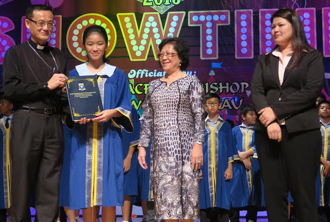 Archbishop Wong poses with one of the graduating students and the school head after the presentation of certificate.